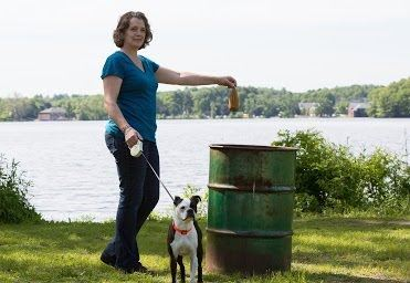 Woman Dropping Dogs Poop Bag in Trash
